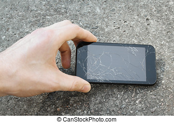hand pick up the mobile phone with broken display