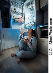 woman sitting on floor at kitchen and having late dinner