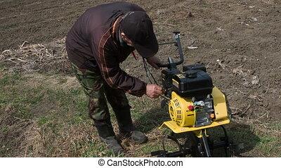 Motor cultivator - man to start the cultivator motor