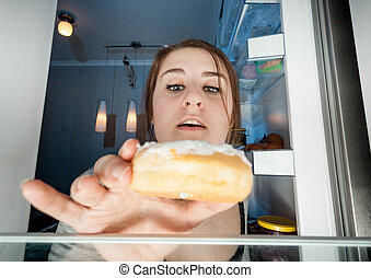 portrait of woman taking donut from fridge - Wide angle...
