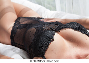 woman torso - young woman torso with black lingerie on bed