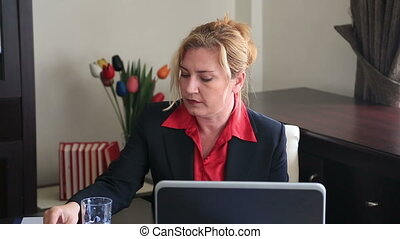 Businesswoman taking pill - Overworked businesswoman taking...