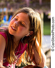 Little girl listening music outdoors