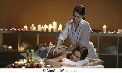 Back Massage - Young lady lying on spa couch massaged by...