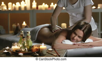 Thai Spa - Groomed woman lying on daybed massaged by...