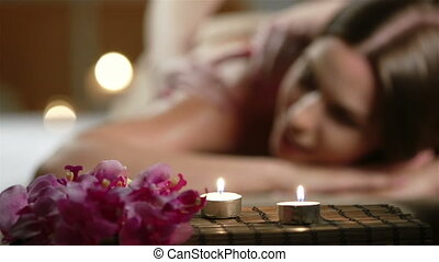 Spa Salon - Close up of flowers and candles, spa therapist...