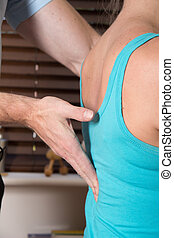closup of chiropractor hand female patient spine -...