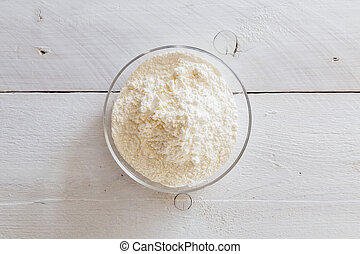 Flour in a bowl on wooden table