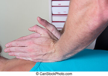 Chiropractor busy treating patients back - Chiropractor...