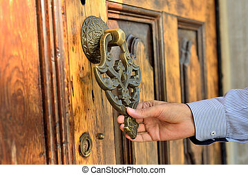 Brass gate with door knocker istanbul Turkey - hand holding...