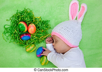 Beautiful sleeping baby in an Easter Bunny outfit alongside...