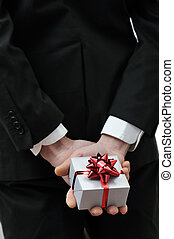 gift box in the hands of a elegant man