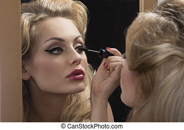 aristocratic girl applying mascara on mirror - close-up...