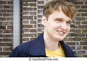 Handsome young man against brick wall smiling Candid