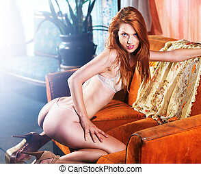 sexy petite red head posing on couch