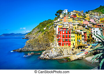 Riomaggiore village on cliff rocks and sea at sunset,...