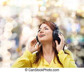 smiling young girl in headphones at home - technology, music...