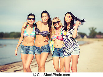 girls in bikinis walking on the beach - summer, holidays,...