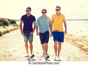 group of friends walking on the beach - summer, holidays,...