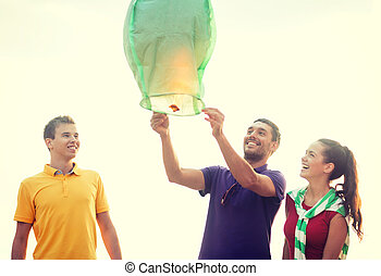 friends with chinese sky lanterns on the beach - summer,...