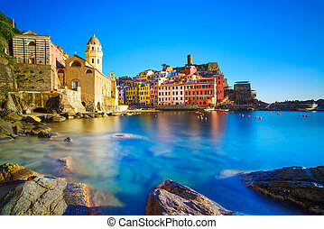 Vernazza village, curch, rocks and sea harbor on sunset,...