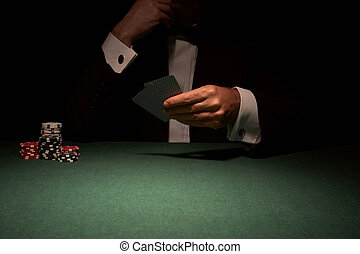 Card player in casino about to play hand of cards