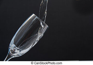 Drinking Glass - Pour water into the glass on a black...