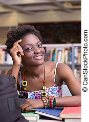 African American Student at the Library studying - Young...