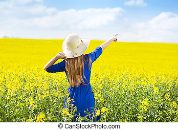 Girl in colza field - Happy young girl in blue dress and...