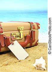 Closed suitcase with empty tag on tropical beach background