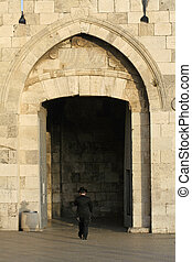 jerusalem - orthodox jew entering jerusalem old city through...