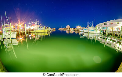 Boats and pier on bay at night