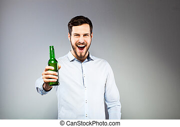 Portrait of a smart serious young man drinking beer - happy...
