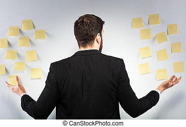 Man standing next to a wall with postits - young businessman...