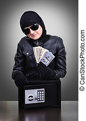 Thief holding a stolen dollars isolated on black