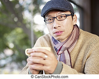 man in coffee shop - man with peaked cap and scarf holding...