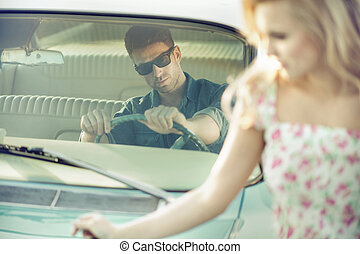 Handsome and stylish man giving young woman a lift -...