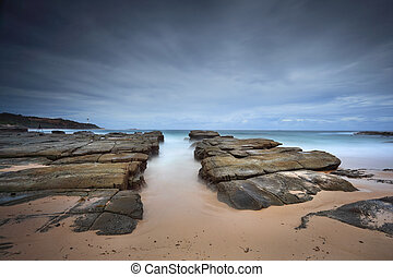 Stormy beach with natural rock channel Soldiers Beach point...