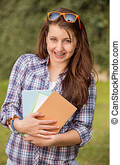 Happy student with braces holding books outside - Happy...