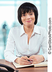 asian smiling businesswoman sitting at table holding...