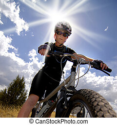 Woman Mountain Biking and Sunshine