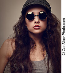 Sexy cool female model in sun glasses. Vintage portrait