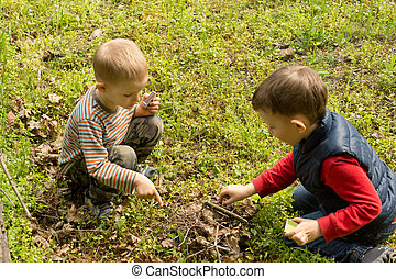 Teamwork as two young boys build a fire together outdoors on...