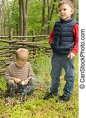 Two young boys learning survival skills trying to light a...