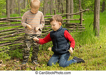 Two young friends playing in woodland building and lighting...