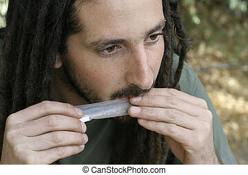 drugs - hippy preparing, rolling and smoking marijuana joint...