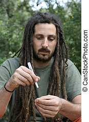 hippy preparing, rolling and smoking marijuana joint :...