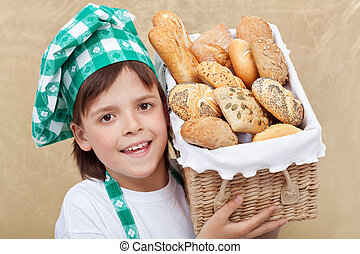 Happy baker boy holding basket with fresh bakery products -...