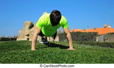 Athlete doing push ups in park - Muscular man exercesing...