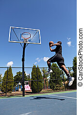 Basketball Dunk - Young basketball player drives to the hoop...